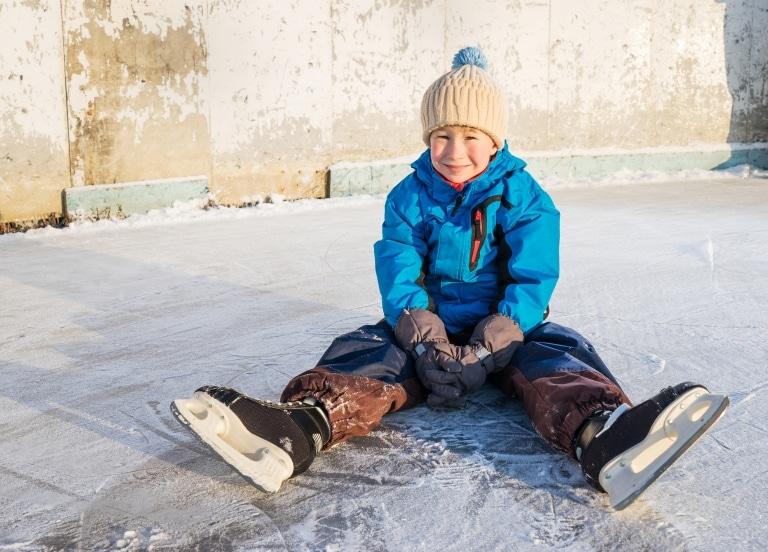 Symbolbild Eislaufen in Landeck: kleiner Junge mit Schlittschuhen sitzt auf der Eislaufbahn