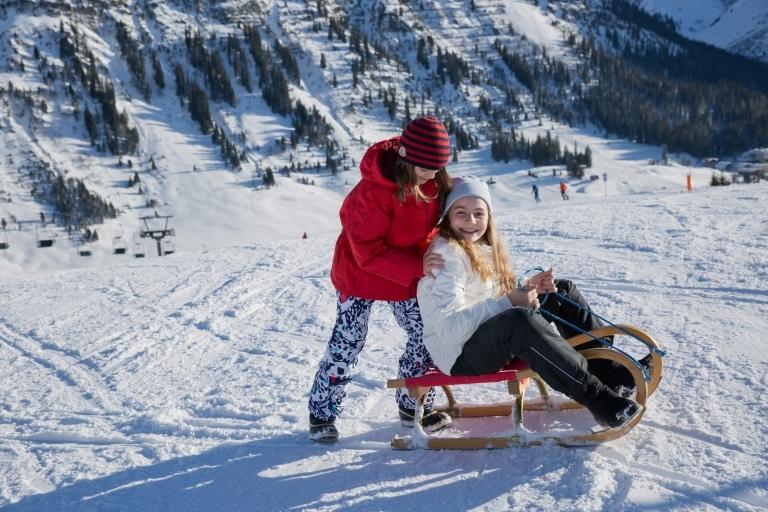 Symbolbild Rodeln in Landeck und Umgebung: zwei Mädchen im Winterurlaub beim Rodeln im Tiroler Oberland