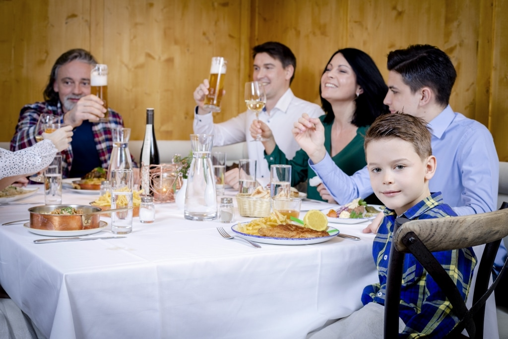 """Eine Familie genießt ein gemeinsames Abendessen im Landecker Restaurant """"Das Landegger"""" im Hotel Schrofenstein."""