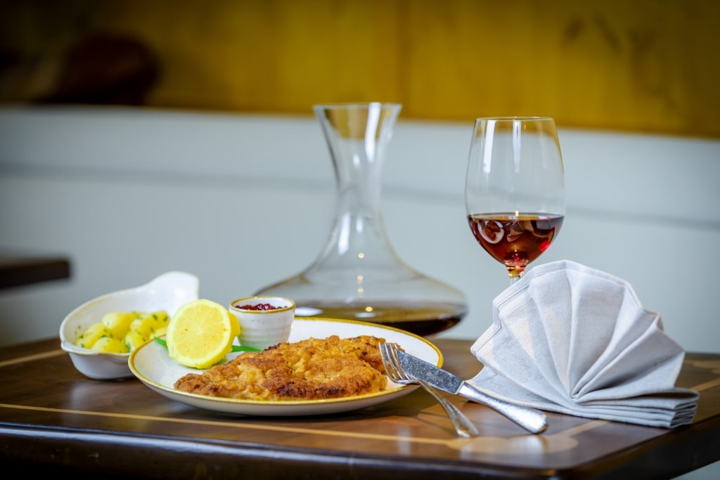 Wiener Schnitzel vom heimischen Kalb mit Petersilerdäpfel und Preiselbeeren im Landecker Restaurant im Hotel Schrofenstein